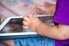 Il neonato sta sedendosi sul pavimento che gioca con il pc della compressa Foto del primo piano delle mani Poco cuscinetto di toc Fotografia Stock Libera da Diritti