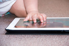 Il neonato sta sedendosi sul pavimento che gioca con il pc della compressa Foto del primo piano delle mani Poco cuscinetto di toc Fotografia Stock