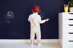Il neonato sveglio della testarossa che attinge il gesso mura a casa fotografie stock libere da diritti