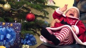 Il neonato sveglio in vestito da natale cade addormentato sulle mani della madre archivi video
