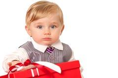 Il neonato tiene un grande contenitore di regalo rosso Fotografie Stock