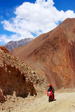 Il Nepal, Himalaya, il regno del mustang superiore - aprile 2015: Un motociclista su un motociclo guida una strada della montagna Fotografie Stock Libere da Diritti