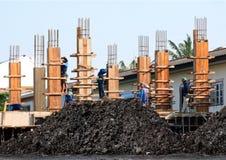 Il nero bagnato dell'argilla ed il cantiere, i muratori, lavoro della gente stanno lavorando alla costruzione della costruzione immagine stock libera da diritti