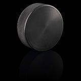 Il nero del disco di gomma di hokey del ghiaccio Fotografia Stock