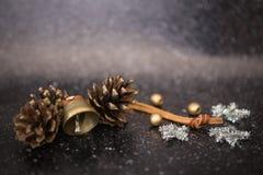 Il nero del fondo di Natale con una campana del metallo e due pini, stelle dei fiocchi di neve dell'argento e palle scintillanti  Fotografie Stock Libere da Diritti