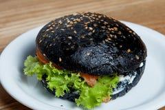 Il nero dell'hamburger con il salmone Fotografia Stock