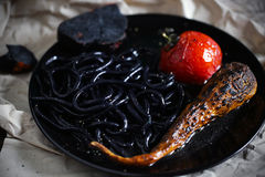 Il nero dell'inchiostro del calamaro ha colorato le tagliatelle con il pomodoro carbone-grigliato, creativo immagini stock