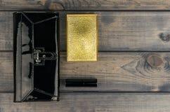 il nero della Borsa-frizione, scatola della polvere con lo specchio e rossetto l dorata Immagine Stock