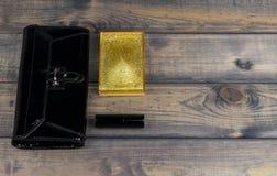 il nero della Borsa-frizione, scatola della polvere con lo specchio e rossetto l dorata Fotografia Stock Libera da Diritti