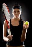 Il nero della palla della racchetta della tenuta di sport della donna di tennis Fotografie Stock