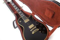 Il nero e chitarra elettrica dell'oro in cassa rossa Fotografie Stock