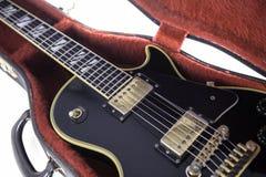Il nero e chitarra elettrica dell'oro in di cassa foderata di pelliccia rossa Immagini Stock Libere da Diritti