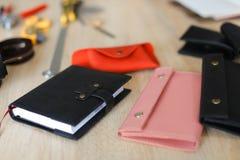 Il nero e portafogli alla moda di cuoio fatti a mano e taccuino di rosa che si trovano sulla tavola Fotografia Stock Libera da Diritti