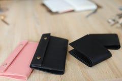 Il nero e portafogli svegli e taccuino di cuoio fatti a mano di rosa che si trovano sulla tavola Immagini Stock