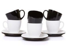 Il nero sulle tazze bianche con i piatti della pila Fotografia Stock Libera da Diritti