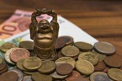 Il netske Hotei della mascotte conia le euro banconote su una tavola di legno Immagine Stock Libera da Diritti