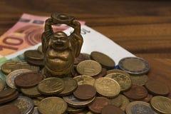 Il netske Hotei della mascotte conia le euro banconote su una tavola di legno Immagini Stock Libere da Diritti