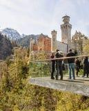 Il Neuschwanstein, Germania - 21 aprile 2016: Un gruppo di turisti su un plateau scenico davanti al castello famoso del Neuschwan Fotografia Stock