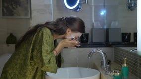 Il nightrobe d'uso castana soddisfatto attraente lava la crema fuori dal fronte in hotel stock footage