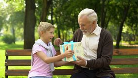 Il nipote dà il regalo di compleanno al nonno, all'amore ed all'attenzione alla gente anziana video d archivio