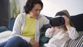 Il nipote sta giocando con nuova tecnologia digitale dei vetri di simulazione di realtà virtuale video d archivio