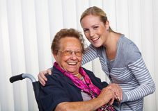 Il nipote visualizza la nonna in una sedia a rotelle Fotografie Stock