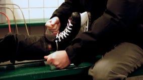 Il nonno aiuta il suo nipote ad allacciare i suoi pattini del hockey su ghiaccio sul banco in casa di riscaldamento della pista d video d archivio