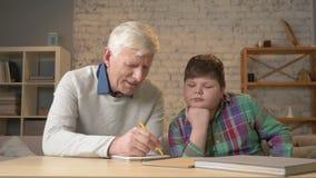 Il nonno aiuta un nipote con compito L'uomo anziano aiuta un giovane bambino grasso a fare il compito Comodità domestica, idillio video d archivio