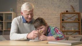 Il nonno aiuta un nipote con compito L'uomo anziano aiuta un giovane bambino grasso a fare il compito Comodità domestica, idillio stock footage