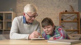 Il nonno aiuta un nipote con compito L'uomo anziano aiuta un giovane bambino grasso a fare il compito Comodità domestica, idillio archivi video