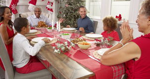 Il nonno dice la tolleranza mentre la famiglia si siede intorno alla tavola che si tiene per mano al pasto di Natale stock footage