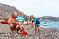Il nonno e due ragazzi del bambino sull'oceano tirano Fotografia Stock Libera da Diritti