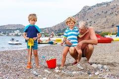 Il nonno e due ragazzi del bambino sull'oceano tirano Fotografie Stock