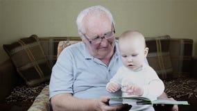 Il nonno e la neonata stanno leggendo un libro video d archivio