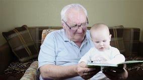 Il nonno e la neonata stanno leggendo un libro stock footage