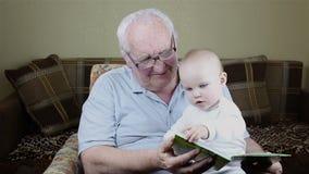 Il nonno e la neonata stanno leggendo un libro archivi video
