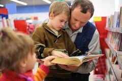 Il nonno ed il nipote e la ragazza hanno letto il libro fotografia stock