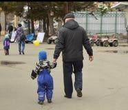 Il nonno ed il nipote che camminano nella città parcheggiano, prendendo la cura dei bambini, il giorno del ` s del padre, nonno Immagine Stock
