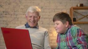 Il nonno ed il nipote stanno sedendo sullo strato e stanno guardando un film divertente sul computer portatile Comodità domestica archivi video
