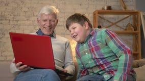 Il nonno ed il nipote stanno sedendo sullo strato e stanno guardando un film divertente sul computer portatile, ridente Comodità  archivi video