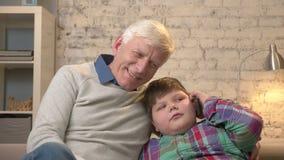 Il nonno ed il nipote stanno sedendo sullo strato Un giovane ragazzo grasso sta parlando su uno smartphone Comodità domestica, di video d archivio