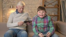 Il nonno ed il nipote stanno sedendo sullo strato Un uomo anziano utilizza una compressa, giochi grassi giovani di un tipo sul vi stock footage