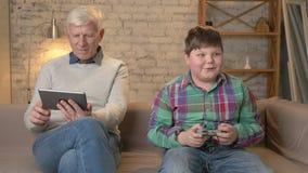 Il nonno ed il nipote stanno sedendo sullo strato Un uomo anziano utilizza una compressa, giochi grassi giovani di un tipo sul vi video d archivio
