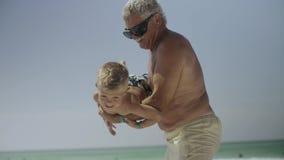 Il nonno ed il suo nipote si divertono sulla spiaggia 4k stock footage