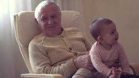 Il nonno felice tiene un bambino sul movimento lento di concetto di felicità della generazione delle mani all'interno archivi video