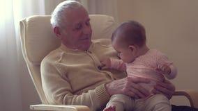 Il nonno felice tiene un bambino sul movimento lento di concetto di felicità della generazione delle mani all'interno video d archivio