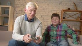 Il nonno gioca nel video gioco della console che si siede sullo strato con il suo nipote Un uomo anziano si siede sullo strato e video d archivio