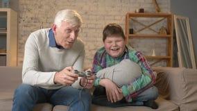 Il nonno gioca nel video gioco della console che si siede sullo strato con il suo nipote Un uomo anziano si siede sullo strato e stock footage