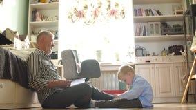 Il nonno guarda l'album di foto con le sue nozze, ragazzino che per mezzo della compressa elettronica archivi video