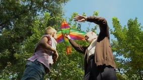 Il nonno insegna al nipote a lanciare l'aquilone, giocante insieme nel parco, hobby video d archivio